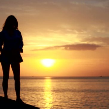 happy woman, pondering life, overlooking the water at sunset