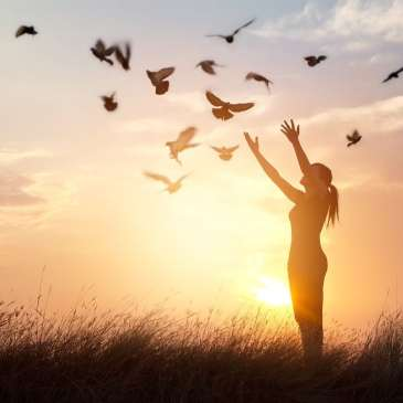 woman releasing doves into the air, liberating them