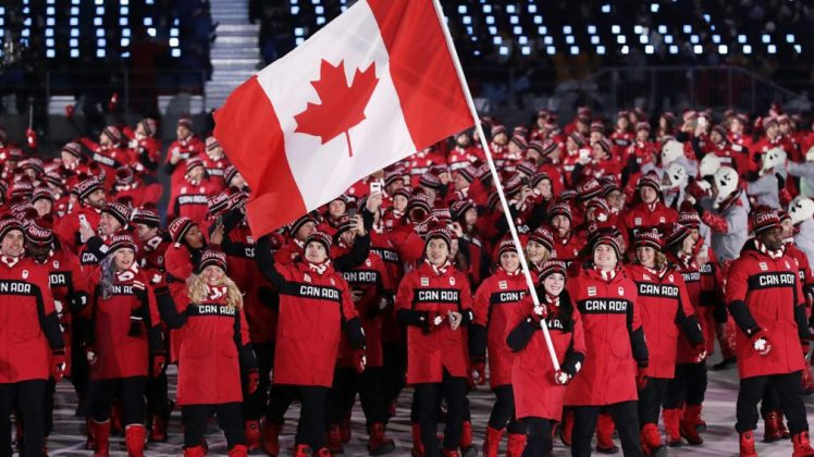 Team Canada athletes smile while holding Canadian Flag