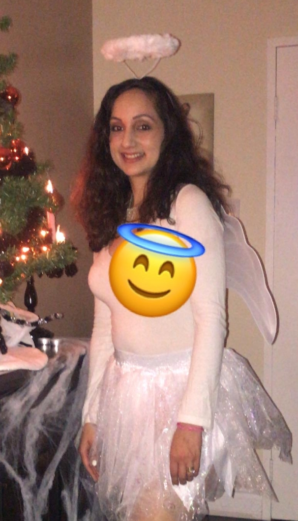 Girl dressed up in an angel costume poses for a photo.