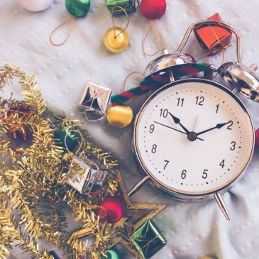 a clock surrounded by holiday decor