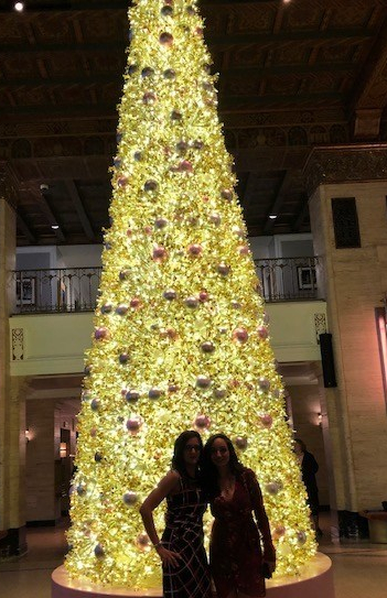 Two ladies at OpportuniTEA infront of large Christmas tree