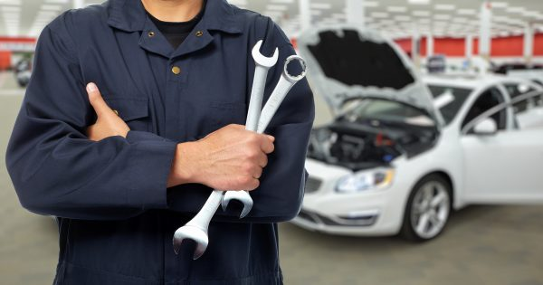 A mechanic with his tools infront of a white car with its hood open.